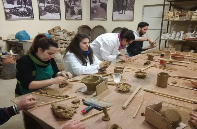 students creating pottery with clay