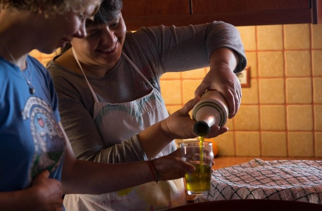 a woman fills a glass with olive oil at the cooking class tour