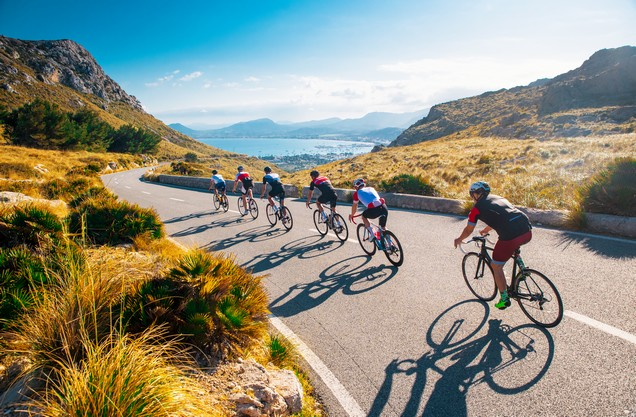 team of cyclists on a country road overlooking the sea