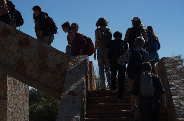 a group of people climbing the steps of the farm entrance