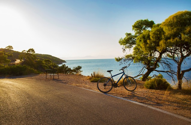 a bicycle parked on the side of the road overlooking the sea
