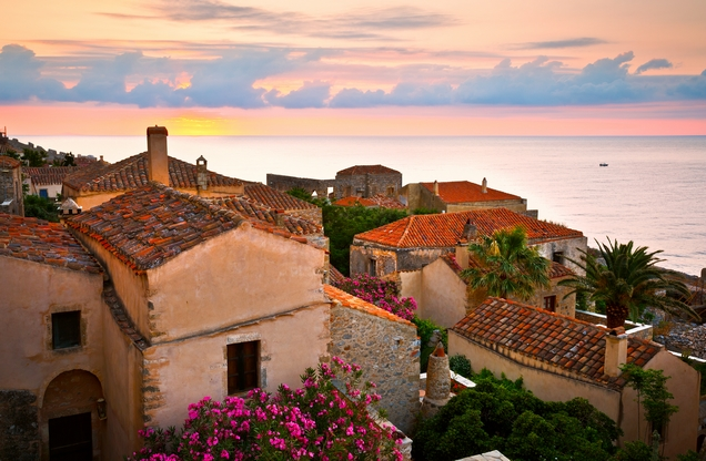 view of the sea above the tiled roofs of houses in Monemvasia