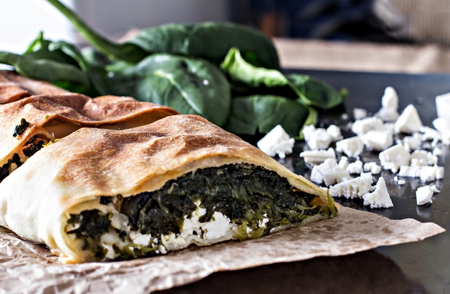 food tasting Greek traditional spinach pie cut on wooden plate