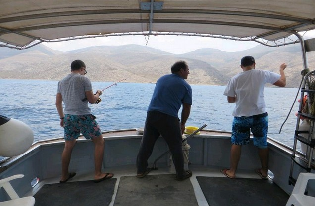 men are fishing on a boat ride in Nafplio