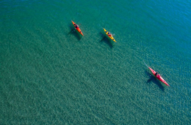 Sea Kayaking in Navarino bay: three people are kayaking in the turquoise waters of Navarino