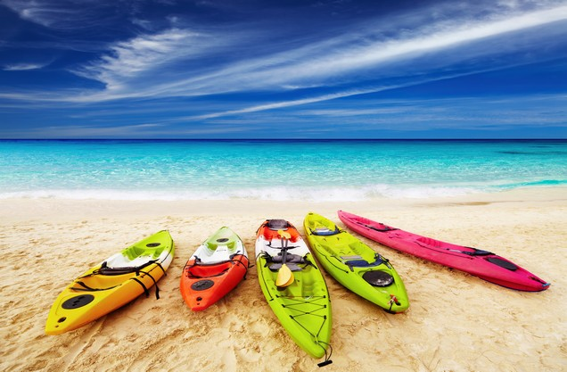 Sea Kayaking in Kalamata: five colored kayaks canoes lined up on the sand in Kalamata