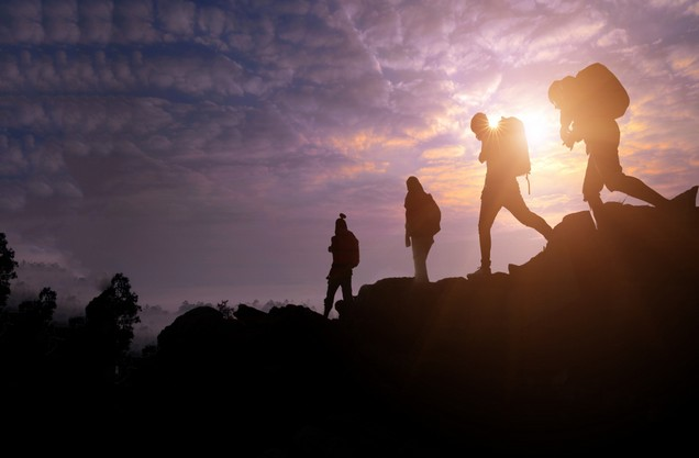 hikers descend from a hill at sunset