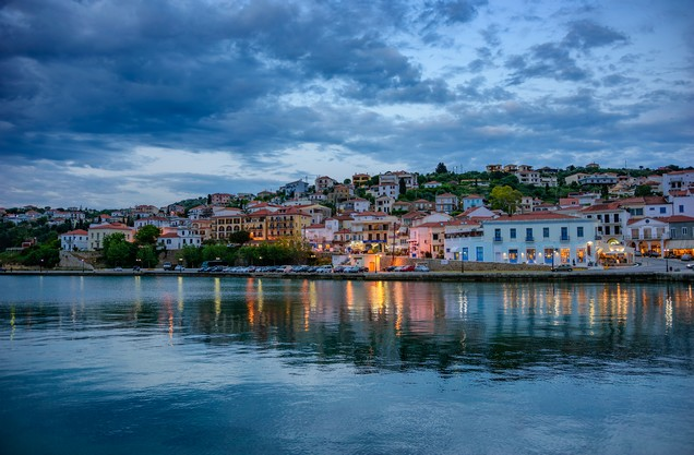 view of the illuminated city of Pylos through the sea