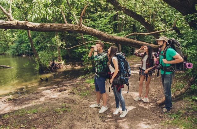hikers look through binoculars around the Neda River