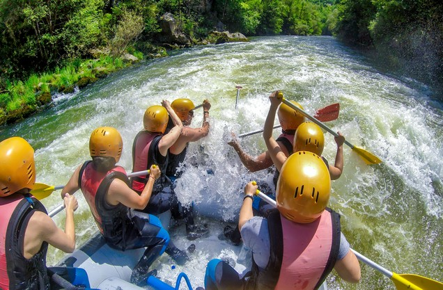A group of people are rafting on the Lousios River