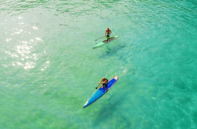 two people do SUP in the blue-green waters of Voidokilia
