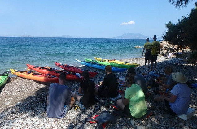 people are sitting on the pebbles of Epidaurus beach and in front of them there are colorful canoes