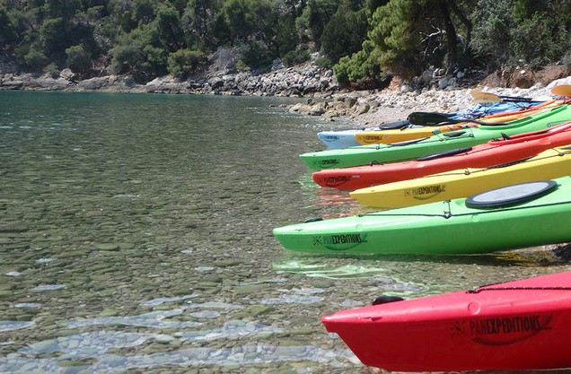 colored canoes lined up on the beach of Epidaurus