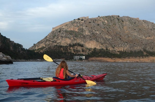 a woman kayaks in the sea infront of the castle of Nafplio
