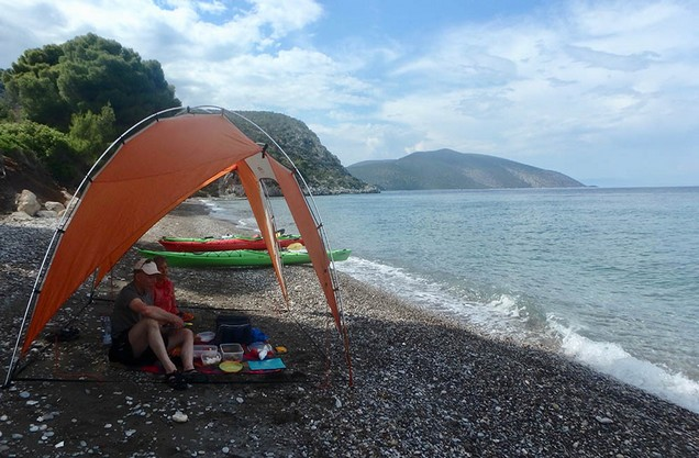 vacationers with canoes and awnings on the beach of Epidaurus