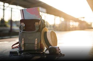 Φτιάξτε τη περιήγησή σας: ένα ταξιδιωτικό σακίδιο με έναν χάρτη και ένα καπέλα ακουμπισμένα δίπλα του