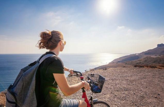 κοπέλα κάνει ποδήλατο δίπλα από την θάλασσα σε ποδηλασία στην Επίδαυρο