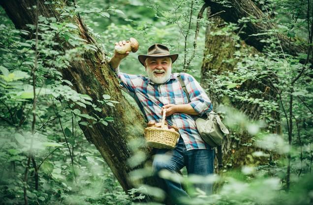 ένας άνδρας κρατάει στα χέρια του ένα καλάθι γεμάτο με φρέσκα μανιτάρια