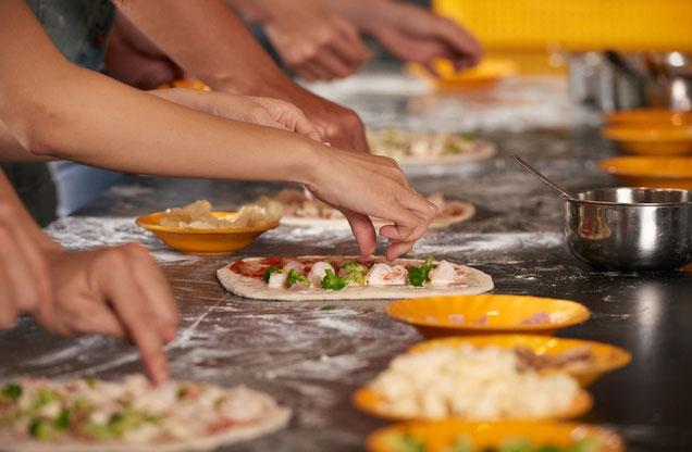 άνθρωποι ετοιμάζουν γεύμα πάνω σε πάγκο μαγειρικής