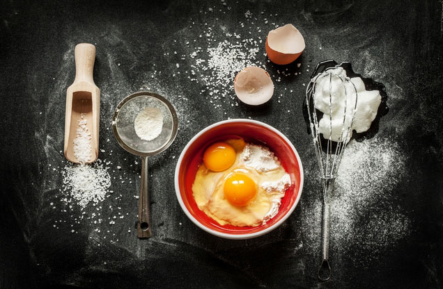 Cooking Class Ναύπλιο: μπολ γεμισμένο με αλεύρι και αυγά ακουμπισμένο πάνω σε μαύρο πάγκο μαγειρικής