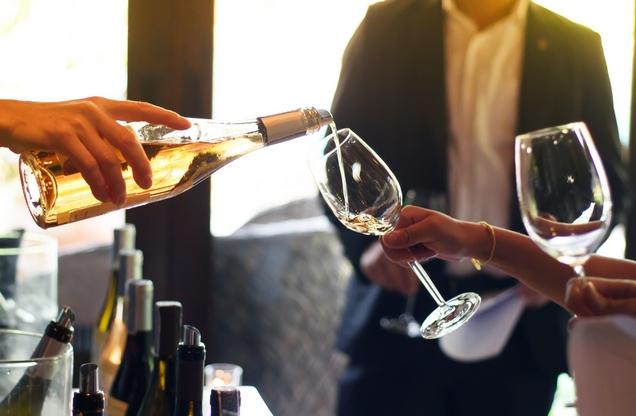 ρίχνοντας λευκό κρασί σε ένα ποτήρι σε μια γευστική εκδρομή στο Ναύπλιο