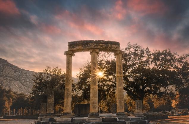 ηλιοβασίλεμα πίσω από τμήμα ναού στην Αρχαία Ολυμπία