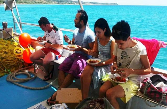 άνθρωποι δοκιμάζουν τα θαλασσινά που ψάρεψαν στο καΐκι στο Ναύπλιο