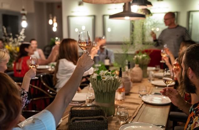 Ομάδα φίλων κάνει πρόποση με ποτήρια κρασί