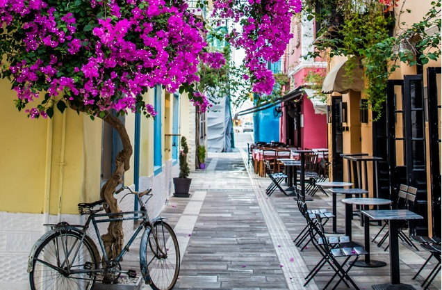 πέτρινο σοκάκι με ανθισμένα μοβ δέντρα στο Ναύπλιο