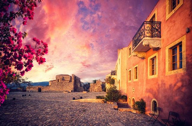 Κάστρο Μονεμβασιάς από Ναύπλιο: κτίρια φωτισμένα από το φως του ήλιου το ηλιοβασίλεμα στη Μονεμβασιά