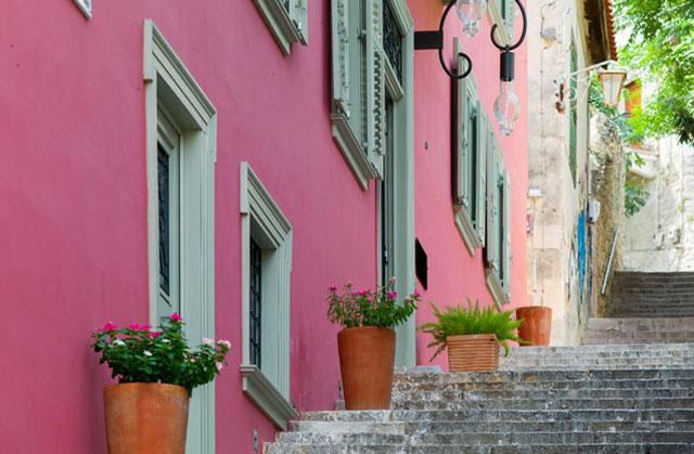 Περίπατος στο Ναύπλιο: πλακόστρωτο σοκάκι στο Ναύπλιο δίπλα σε ροζ νεοκλασικό κτήριο