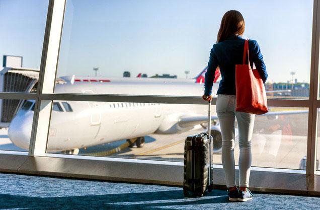 Αεροδρόμιο Αθήνας Ελ.Βενιζέλος από ή προς Πάτρα: μια κυρία με τις αποσκευές της κοιτάζει έξω από το τζάμι τα αεροπλάνα στο αεροδρόμιο της Αθήνας