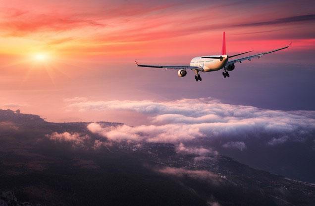 Αεροδρόμιο Αθήνας Ελ.Βενιζέλος από ή προς Ολυμπία: ένα αεροπλάνο πετάει ανάμεσα στο σύννεφα την ώρα που δύει ο ήλιος