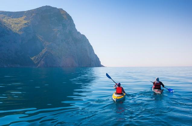 Καγιάκ στην Καρδαμύλη: δυο άνθρωποι κάνουν καγιάκ στα γαλάζια νερά της θάλασσας της Καρδαμύλης