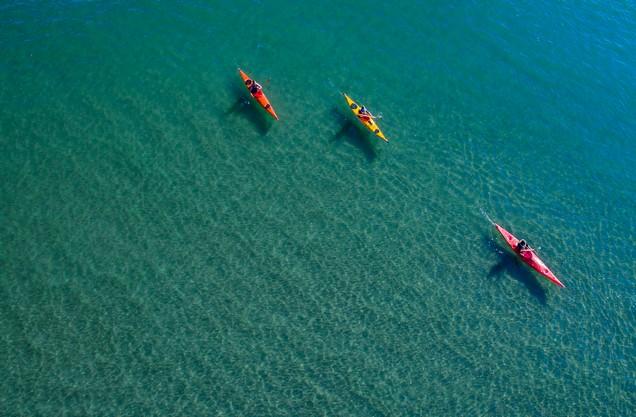 Καγιάκ στον όρμο του Ναυαρίνου: τρεις άνθρωποι κάνουν καγιάκ στα γαλαζοπράσινα νερά του Ναυαρίνο
