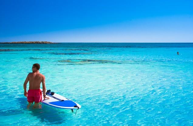SUP & Snorkeling στην Καρδαμύλη: ένας άνδρας με την σανίδα του στα καταγάλανα νερά της Καρδαμύλης