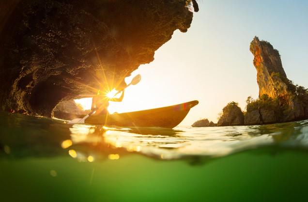 ο ήλιος μέσα από το νερό της θάλασσας και ένα κανό