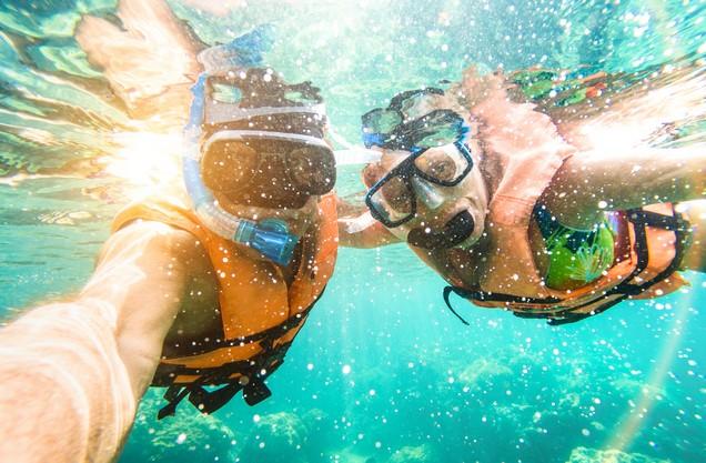 ένα ζευγάρι κάνει βουτιά στη θάλασσα φορώντας μάσκα θαλάσσης