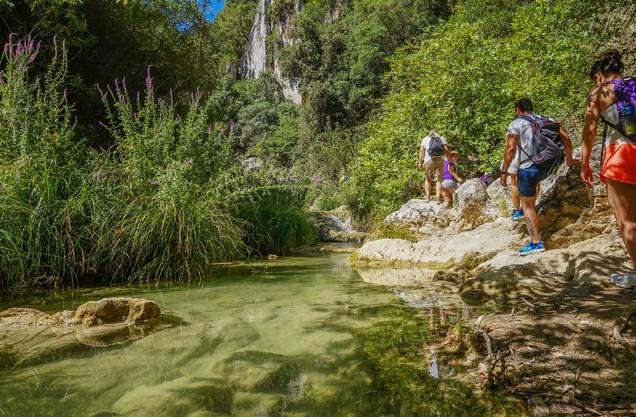 άνθρωποι περπατούν διπλα από τα τρεχούμενα νερά στο Πολυλίμνιο