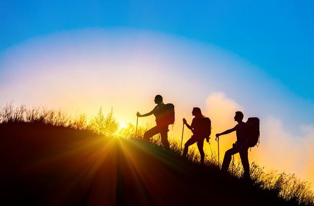 πεζοπόροι σε λόφο την ώρα του ηλιοβασιλέματος