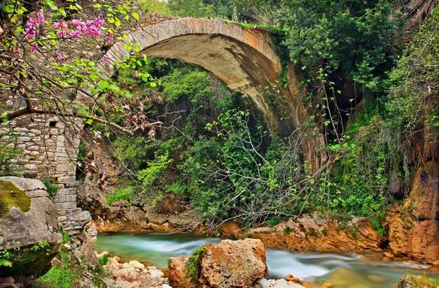 μια γραφική πέτρινη γέφυρα πάνω από τον ποταμό της Νέδας