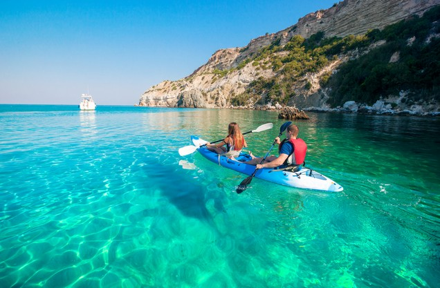 δυο άνθρωποι κάνουν καγιάκ στα γαλάζια νερά της θάλασσας της Καρδαμύλης