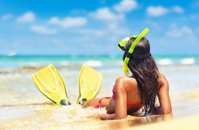μια γυναίκα με βατραχοπέδιλα και μάσκα θαλάσσης ξαπλωμένη στην αμμουδιά