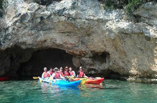 άνθρωποι κάνουν κανό καγιάκ στην παραλία της Επιδαύρου μπροστά από σπήλαιο