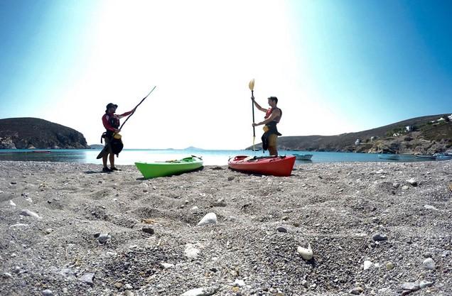 δύο άντρες κρατούν κουπιά για καγιάκ στην παραλία